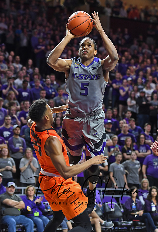 Guard Barry Brown #5 of the Kansas State Wildcats drives to the basket over forward Leyton Hammonds #23 of the Oklahoma State Cowboys during the second half at Bramlage Coliseum in Manhattan, Kansas.