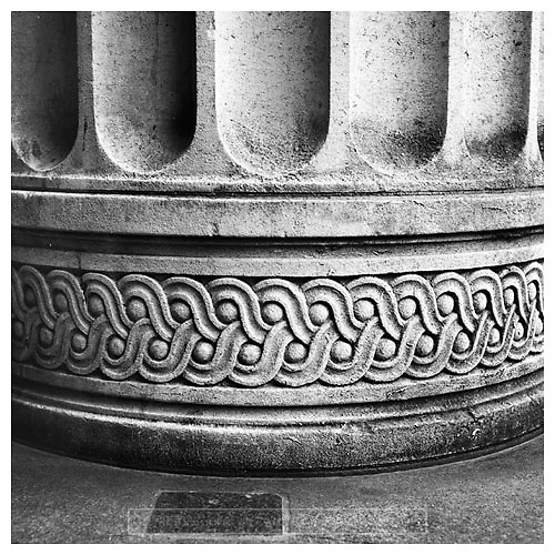 Black and white photograph of the base of a Corinthian Column. Mounted print available to purchase.