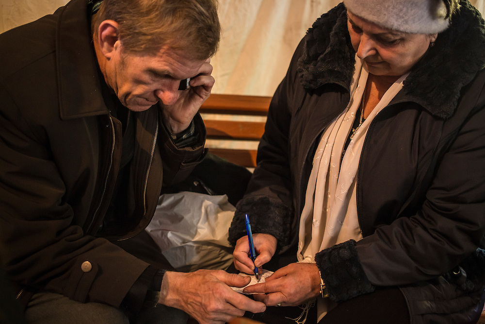 DNIPROPETROVSK, UKRAINE - OCTOBER 11: A couple from Horlivka take notes regarding an apartment they hope to rent as they wait in a tent for the opening of a center to help people displaced by fighting in Ukraine's East on October 11, 2014 in Dnipropetrovsk, Ukraine. The United Nations has registered more than 360,000 people who have been forced to leave their homes due to fighting in the East, though the true number is believed to be much higher. (Photo by Brendan Hoffman/Getty Images) *** Local Caption ***