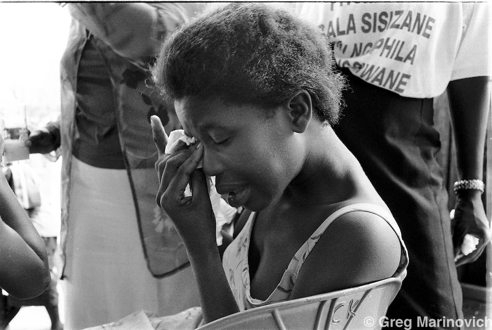 IPMG0563 South Africa, Ngwelezana 2000: .Sixteen year old Thombi Hlongwe is comforted by Nonhlanhla Zungu (an HIV positive Aids activist) as she breaks down after seeing the open casket of AIDS activist Deli Hlongwa in Ngwelezana in the KwaZulu Natal province of South Africa, March 25, 2000 on the day of her funeral.  Deli was a person living with full-blown AIDS who took part in the local `Funeral Campaign' where people with HIV and Aids tell others in he community of their disease and invite them to come look at them in their open casket when they die, to disprove the widely-held notion that HIV does not kill.  South Africa has a rapidly growing HIV crisis, with some 25% of ante-natal women testing positive...Photograph by Greg Marinovich/South Photographs