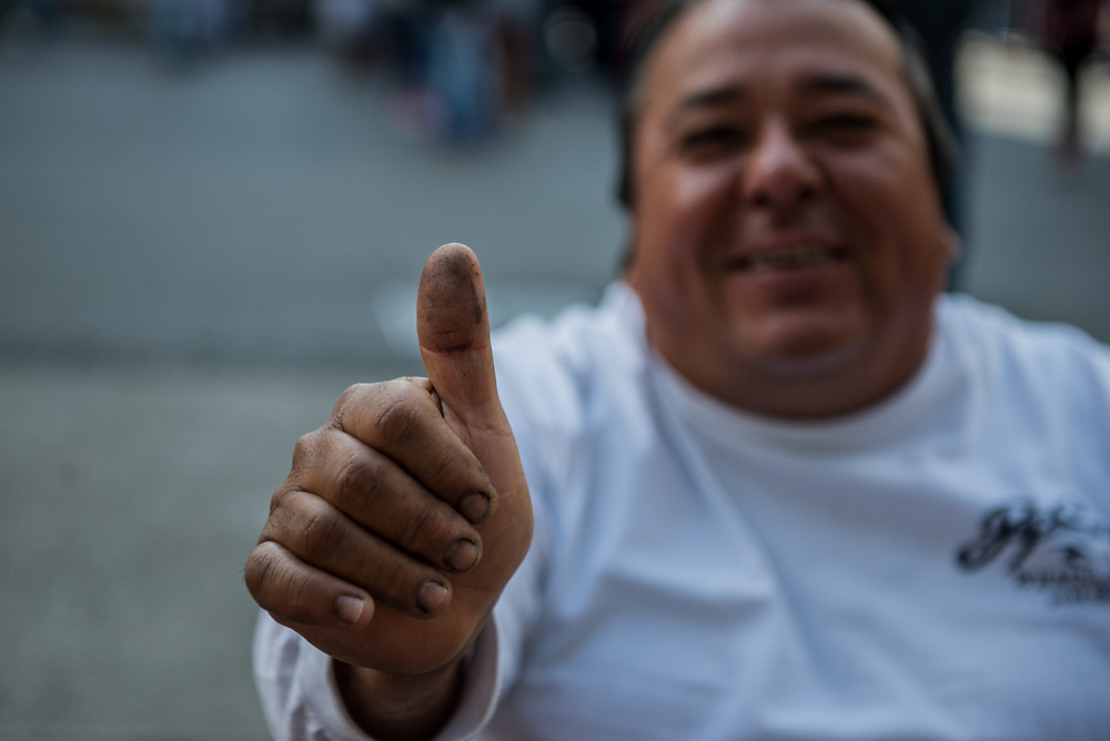 CARACAS, VENEZUELA - JULY 30, 2017:  A government supporter shows his marked thumb that shows he voted for in today's election for candidates for the new National Constituent Assembly, in elections called by Socialist President, Nicholás Maduro. Lines across Caracas were significantly shorter than those of the opposition's July 16th symbolic vote. Many fear this election will turn Venezuela similar to Cuba. Opponents of the government criticize President Maduro for calling for this election - saying the new assembly is a power grab, and will be a puppet of the President - the only candidates on the ballot are government loyalists. Critics also fear the new assembly will turn the country into a dictatorship, re-write the constitution and wipe out the democratically elected and opposition controlled congress. There have been widespread reports of voter intimidation, and of the government threatening state workers and citizens that receive government benefits like subsidized food - who report the government telling them they are obligated to vote, and if they don't, they will lose their jobs and benefits. Thousands have taken to the streets to protest the election in the days leading up to the July 30th vote.  PHOTO: Meridith Kohut for The New York Times