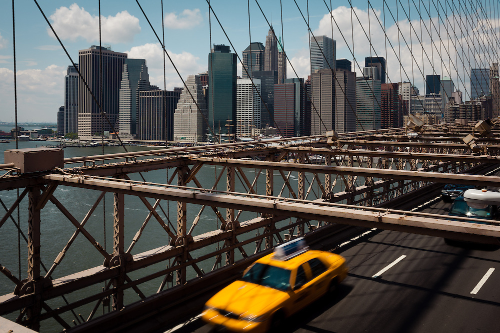 A New York Taxi crosses the Brooklyn Bridge whilst Manhattan and the Statue of Liberty can be seen in the background, New York.