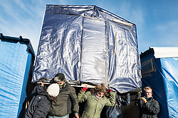 © London News Pictures. Calais, France. 15/01/16. Residents of the Calais 'Jungle' refugee camp clear their belongings and move shelters ahead of the eviction of approximately 1/3 of the camp. French authorities are to bulldoze a 100-metre 'buffer zone' between the camp and the adjacent motorway, which leads to the ferry port. Photo credit: Rob Pinney/LNP