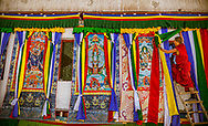 Monk hangs Thangkas before Chaam Festival, Kye Tibetan Buddhist Monastery, Spiti Valley, India