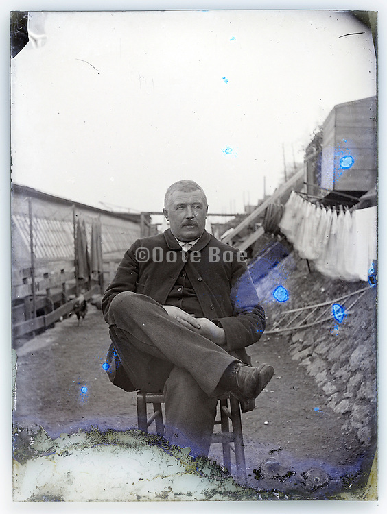 eroding glass plate with adult man sitting outside by river edge 1900s Paris