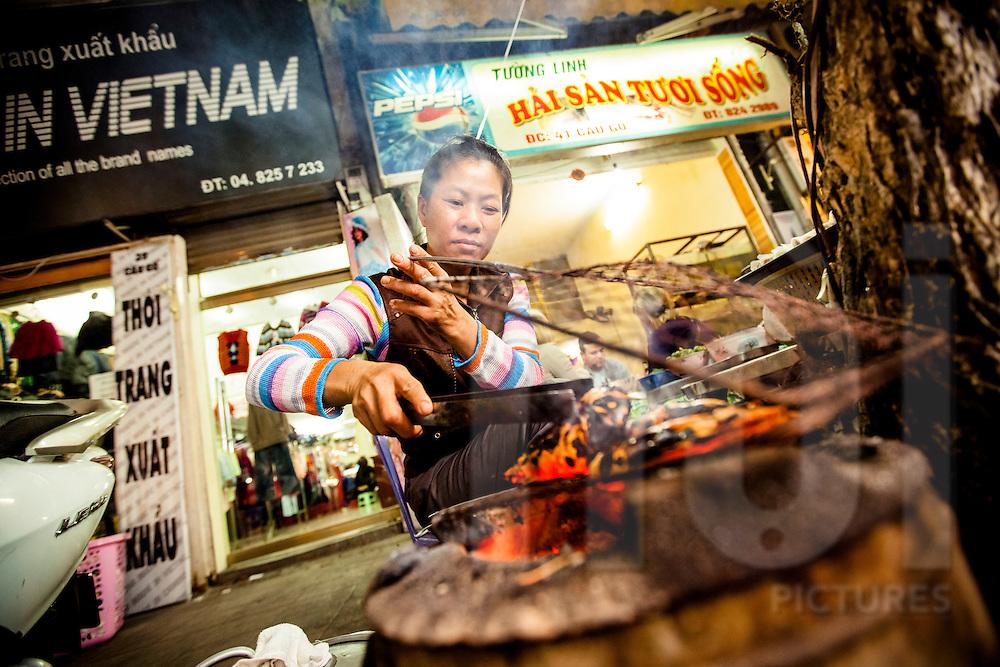 A vietnamese woman grills shrimps in a street of Hanoi, Vietnam, Southeast Asia