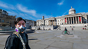 Trafalgar Sqaure is pretty quiet but there are several tourists in masks - Anti Coronavirus (Covid 19) outbreak in London.