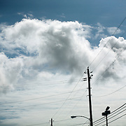 Clouds float in blue skies over power lines.