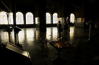 A woman holds a candle and prays inside Alexander Nevsky Cathedral in Sofia, Bulgaria. The cathedral, completed in the early 1900s, was built in honor of Russian and other soldiers who died during the Russo-Turkish War of 1877-1878, in which Bulgaria was liberated from Ottoman rule.