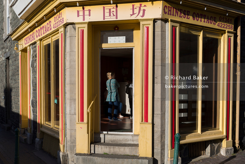 A lady waits for her order in the Chinese Cottage takeaway, on 12th September 2018, in Dolgellau, Gwynedd, Wales.