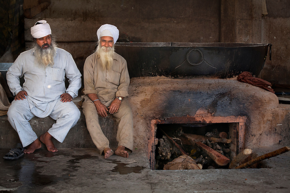 Cooks in a Sikh kitchen,Langar, taking a break. The enormous pots are needed to cook for the tens of thousands of pilgrims who come everyday.
