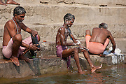 Indian men washing themselves and their clothes in waters of The Ganges River at Kali Ghat in City of Varanasi, Benares, India