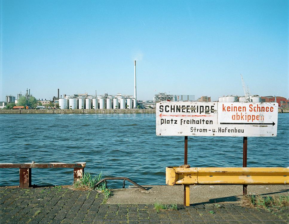 Schneekippe und Ölraffinerie an der Elbe