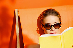 Woman Reading Book whilst Sunbathing