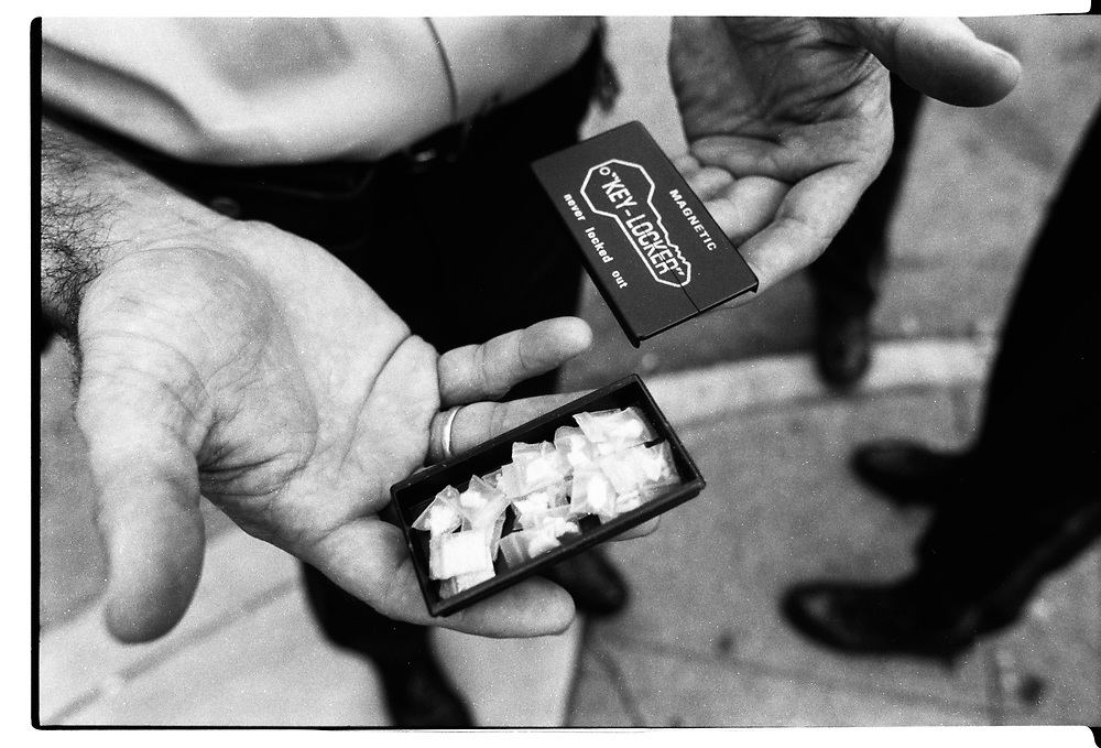 Officer Sweeney holds a hide key holder filled with drugs that was confiscated after watching a drug dealer stash it on a derilect car in West Philadelphia