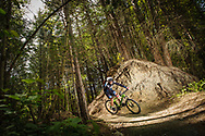 Ole Rasmussen mountain bikes through the woods in New Zealand