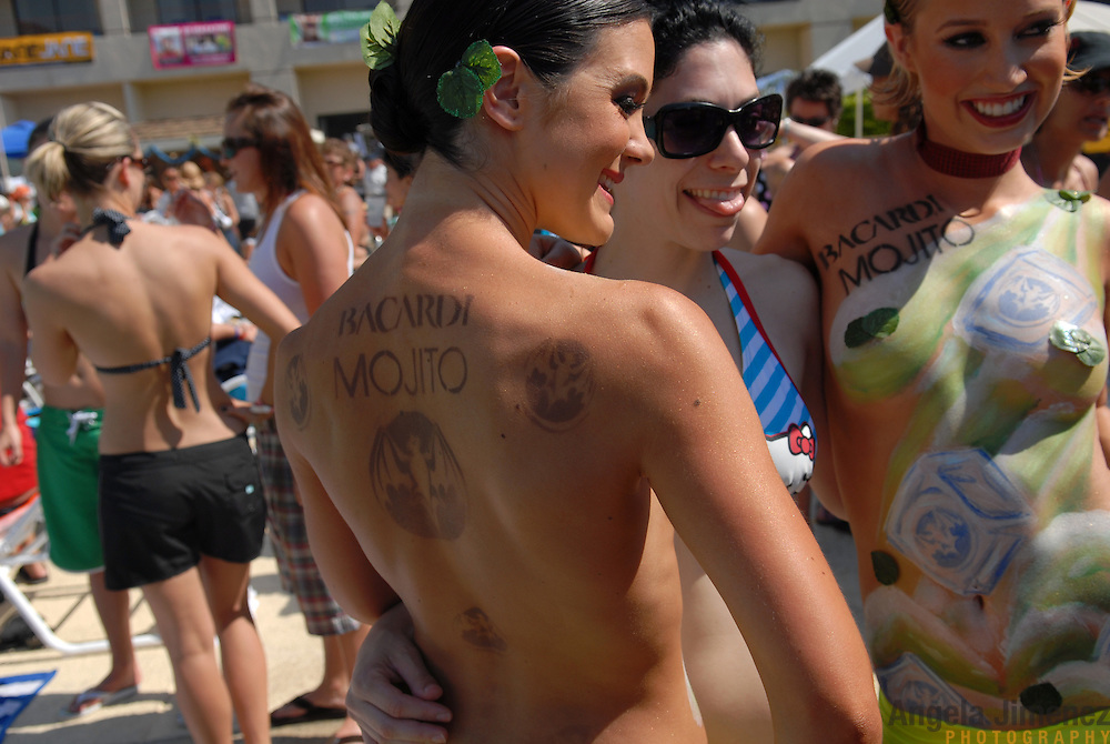 A woman, front center, poses with two Bacardi promo girls, front left and right, with the company's name and logo painted on their bodies, at  the L Word pool party hosted by lesbian party promoter Mariah Hanson's Club Skirts company at the Doral Desert Princess Resort in Cathedral City, California (just outside of Palm Springs), on April 1, 2007, the last of five days of parties at the Dinah Shore weekend, the annual lesbian gathering run simultaneously with the Kraft-Nabisco Championship LPGA golf tournament. .
