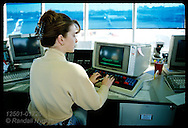 Female flight information coordinator checks schedules in TWA tower; Lambert Airport/St. Louis Missouri