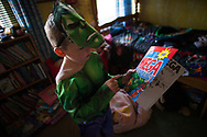 Lucas (5 ) looks at his Avengers book dressed as Hulk  at home in Shefield UK Tuesday, Aug. 12, 2014The D'Arby family is involved in the FAST  (Families and Schools Together) program which encourages parents to read to their children at home.(Elizabeth Dalziel for Save the Children )