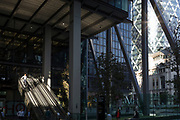 Mid-afternoon sunlight illuminates the escalators of 1, Leadenhall and in the background, the Swiss re Building on St Mary Axe (aka The Gherkin) in the City of London - the capital's financial district, on 10th October 2018, in London, England.