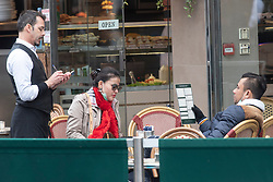 © Licensed to London News Pictures. 17/03/2020. London, UK. Visitors wearing face masks order food from a waiter in an empty Leicester Square cafe. Photo credit: Ray Tang/LNP