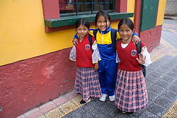 South America, Ecuador, Otavalo,  girls in school uniforms walking home from school