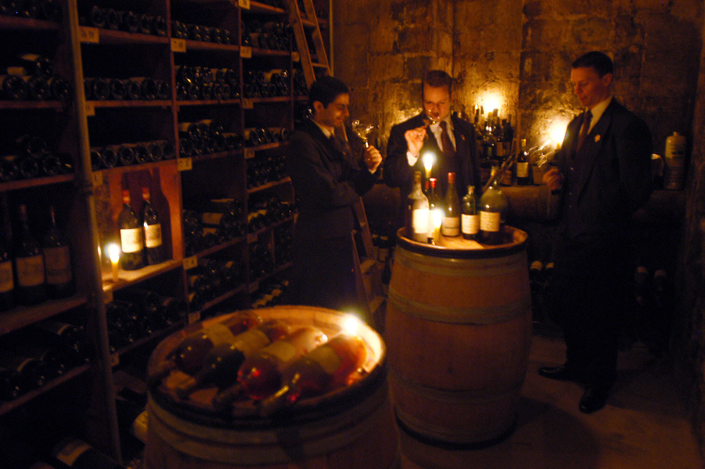 """Three of the restaurant's """"sommeliers,"""" (L to R) Aurelien Gil-Artagnan, Marco Pelletier and Manuel Peyrondet, test wines in the restaurant's wine cellar. The Taillevent restaurant at 15, rue Lamennais, Paris 8e has been awarded three stars in the prestigious Michelin guide...Paris, France. 15/04/2005..Photo © J.B. Russell"""