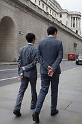 Two businessmen walk past the Bank of England, both with hands clasped behind their backs, in the City of London - the capital's financial district, on 4th June 2018, in London, England.