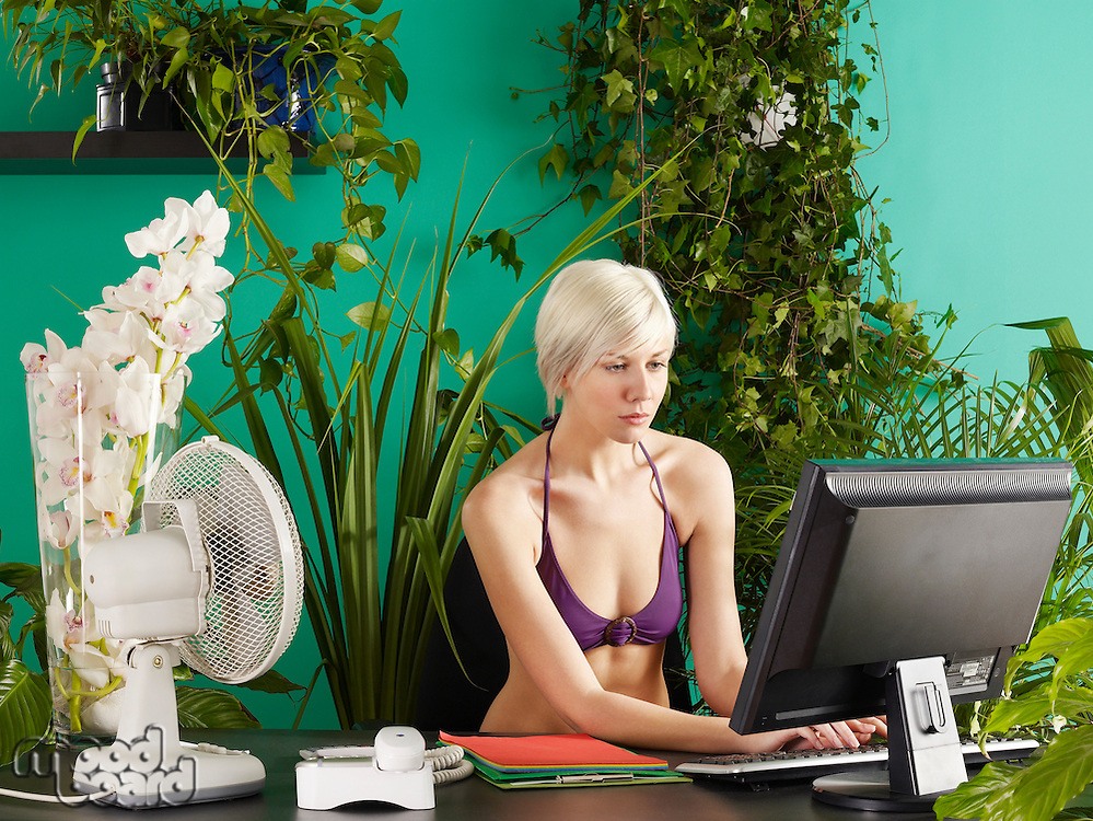 Female office worker wearing bikini sitting behind desk