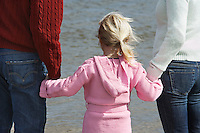 Girl (5-6) holding hands with parents at ocean