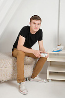 Young man sitting on fur ottoman with video game controller