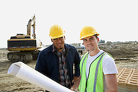 Construction workers with blueprints on site, portrait