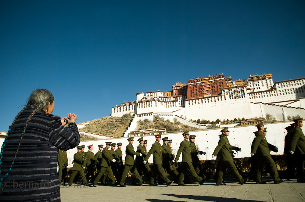 Tibetan woman pray in front of the Potala palace (Dalai lama´s former residence) wile Chinese soldiers march in-front of her in Lhasa, Tibet.
