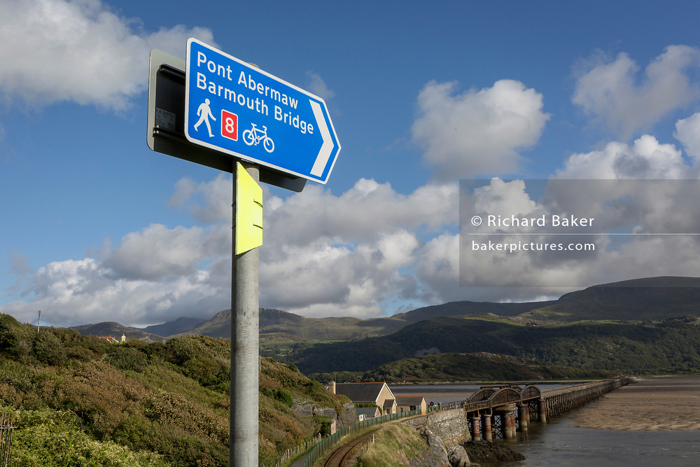 Signpost pointing down towards Barmouth's pedestrian and rail bridge on the Mawddach Estuary, on 13th September 2018, in Barmouth, Gwynedd, Wales.