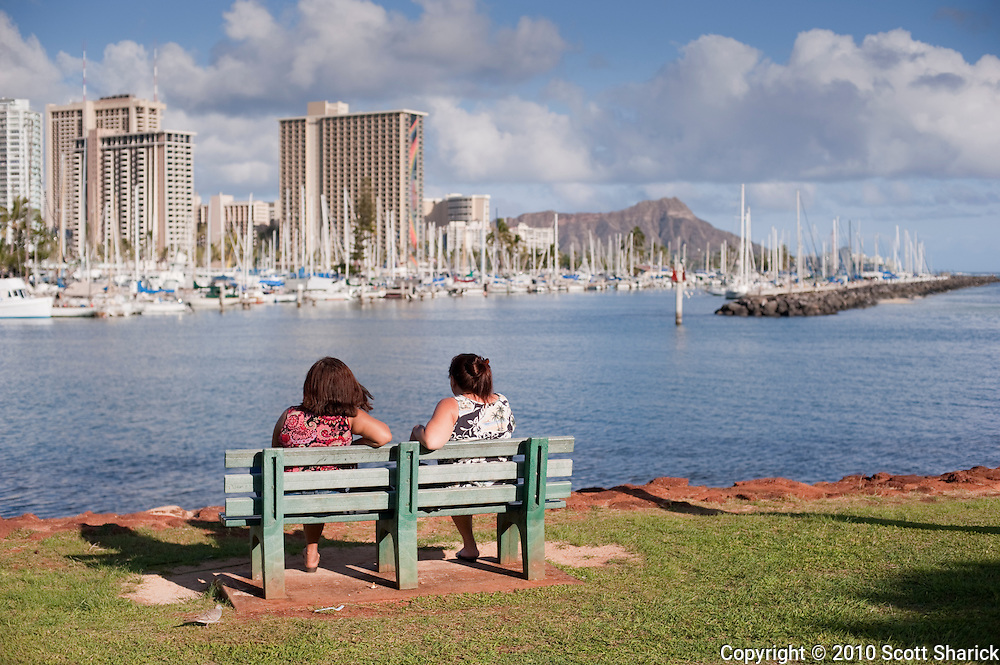 Two women on a bench at Ala Moana Beach Park look towards Waikiki.