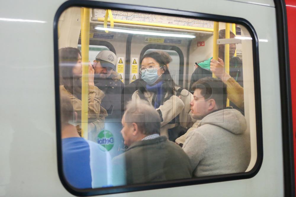 © Licensed to London News Pictures. 14/02/2020. London, UK. A commuter wearing a surgical face mask travels on a  London Underground train as there are fears that the virus could already be on the London Underground. Photo credit: Dinendra Haria/LNP