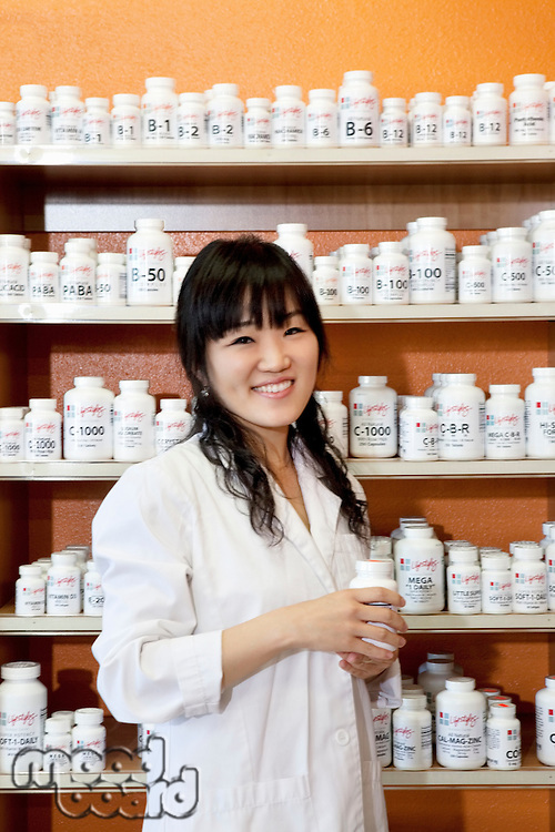 Portrait of a happy young woman with pill bottle in drugstore