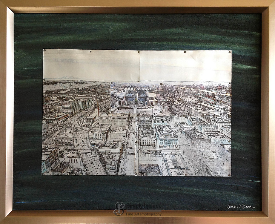 """$150, Stadiums is printed five up-cycled aluminum cans mounted on a 16""""x 20"""" hand painted background and framed."""