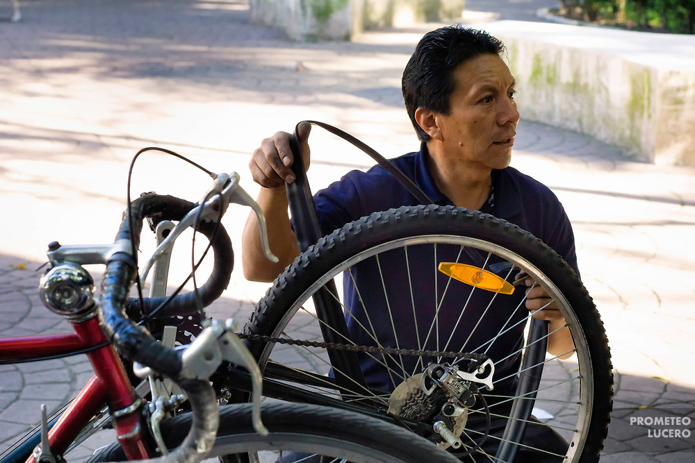 """Vicente Yáñez Tenorio arregla una bicicleta en el Parque México el 7 de noviembre de 2017. Su taller, un negocio familiar de 80 años, se encuentra en la esquina de Sonora y Avenida México, donde un edificio colapsó. Hasta el momento, Yáñez ha recibido solamente 2 mil pesos mexicanos de apoyo del gobierno (aprox 100 USD). // Vicente Yáñez Tenorio fixes a bike in Parque México on November 7th, 2017. His workshop, """"Taller de Bicicletas Orozco"""", an 80-year-old family business, is in the corner of Sonora and Mexico avenue, where a building collapsed. At the moment, the only economical support from city government he has received is 2000 Mexican pesos (100 USD). (Prometeo Lucero)"""