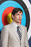 Man with toy arrow on forehead standing in front of target