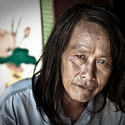 A Chinese man sets and looks at the camera.