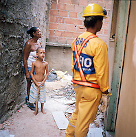 Residents of Largo do Tanque undergo forced evictions and demolition of homes in Rio de Janeiro's West Zone, to make room for the Transcarioca Highway, that will eventually be built to accommodate the Olympics, in Rio de Janeiro, Brazil, on Monday, Feb. 25, 2013. ..In less than 2 weeks, 54 houses were demolished with sledgehammers and bulldozers. The City assessor sent to handle negotiations told residents not to speak with one another or seek legal advice otherwise he would reduce settlement offers. Many residents agreed to compensations, around R$7000 (US$3500). Most residents cannot afford to buy a plot of land with that compensation and will be forced to rent kitchenettes, at less than 20m2. As established in the Brazilian Constitution, and in accordance with local legislation (the Organic Municipal Law), the duration of residents' life in the area gave them legal rights to the homes, while compensation should allow them to attain an equal situation elsewhere. ..The west zone, located west of downtown and beach neighborhoods is often overlooked and is widely known to be run by militia groups, who are former and current police and firefighter personnel that run extortion rings to monopolies. .