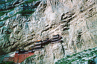 China, Datong, 2008. Suspended from a sheer cliff face by little more than wooden supports and a prayer, the 1400 year old Xuankong Temple is safe above a valley prone to flooding.