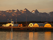 Glacier-clad peaks on a Chilean island located across Beagle Channel catch sunrise, as seen from near Ushuaia airport. Ushuaia is capital city of Tierra del Fuego Province, Argentina, South America.