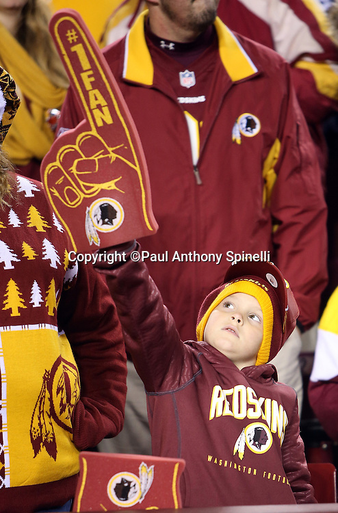 A young Washington Redskins fan holds up a foam finger during the Washington Redskins 2015 week 13 regular season NFL football game against the Dallas Cowboys on Monday, Dec. 7, 2015 in Landover, Md. The Cowboys won the game 19-16. (©Paul Anthony Spinelli)