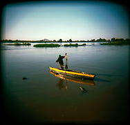 A fisherman casts his net early in the morning on the White Nile.<br /> Juba, South Sudan. 13/10/2009.