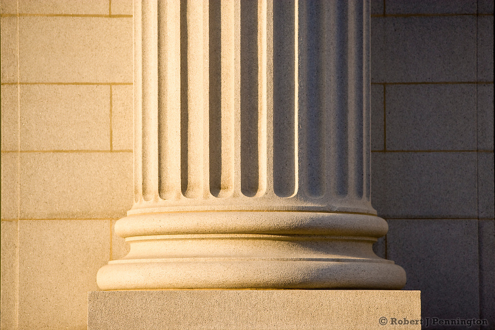 A single stone column on a courthouse with morning sunlight.