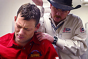 09 DECEMBER 2002 - Darren Clarke, a bareback rider, grimaces in pain as Doug Olle, a trainer with the Justin Boots Sports Medicine Team, loosens him up in the medical room in the basement of the Thomas and Mack Center at UNLV for the 4th round of the National Finals Rodeo Monday evening.  PHOTO BY JACK KURTZ
