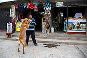 A boy plays with a dog in Maca, Peru.