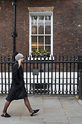London, England, Uk, February 5 2019 - A woman passing in front of a window of The Royal Institute for International Affairs, a Think Tank commonly known as Chatham House.